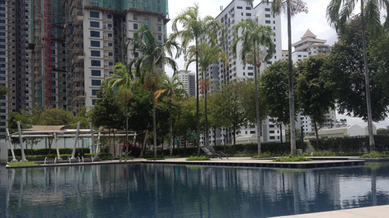 """Picture of a pool surrounded by palm trees and tall apartment buildings with white text saying """"A year of housesitting in SE Asia"""""""