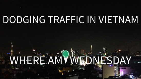"Photo of a city skyline at night with white text in the foreground that says ""Dodging Traffic in Vietnam. Where Am I Wednesday"""