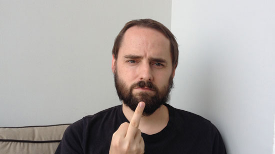 Picture of a white male in a black shirt holding his middle finger up to the camera