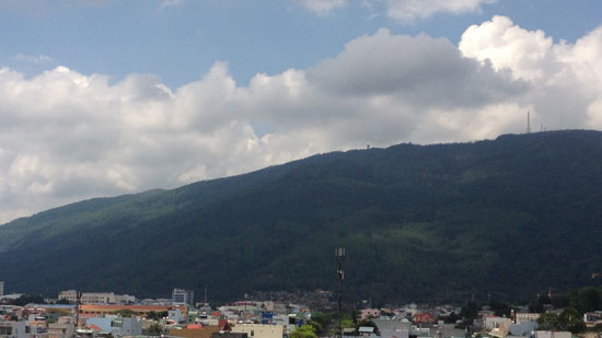 Picture of Quy Nhon, Vietnam with mountains and clouds in the background and city buildings in the foreground.