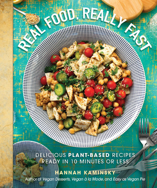 "Cookbook cover with a photo of a meal prepared on a table decorated with cutlery and other things. Text in the foreground says ""Real Food, Really Fast. Delicious plant-based recipes ready in 10 minutes or less. Hannah Kaminsky. Author of Vegan Desserts, Vegan a la Mode, and Easy as Vegan Pie."""