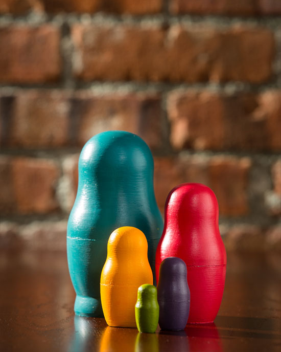 Picture of a series of Matryoshka dolls in front of a red brick wall