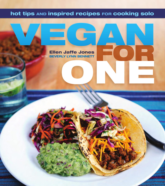 "Image contains a photo of a single taco, guacamole, and a small salad on a plate. In the background, there is a glass of water with lime and a bowl of veggie ground beef. Text above the photo says ""Hot tips and inspired recipes for cooking solo. Vegan For One. Ellen Jaffe Jones with Beverly Lynn Bennett."""