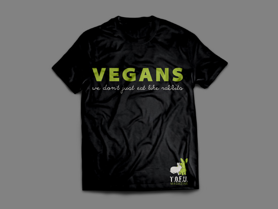"Picture of a black shirt against a grey background. The shirt has green text that says ""Vegans"" and white text below that says ""We don't just eat like rabbits"". In the bottom of the shirt, there are two small rabbits just above the words ""T.O.F.U. Magazine"""