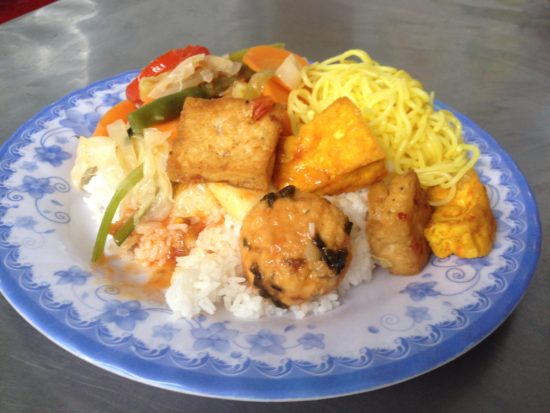 Photo contains a plate of rice with various vegetables, tofu, and noodles placed on top.