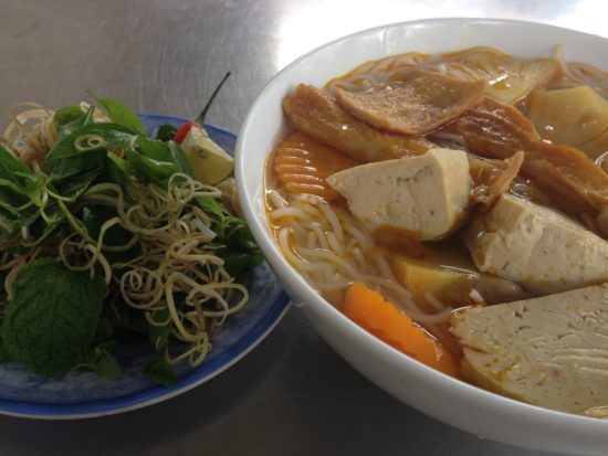Photo contains a bowl of noodles with tofu, carrots, and other vegetables next to a plate of fresh herbs.