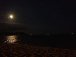 Night photo with the full moon to the left and its reflection in the ocean below.