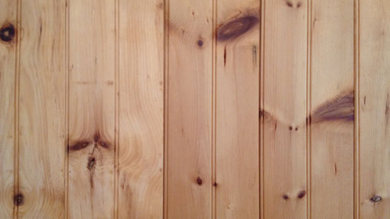 Image contains vertical wood panelling with a number of darker brown knots scattered throughout each panel.
