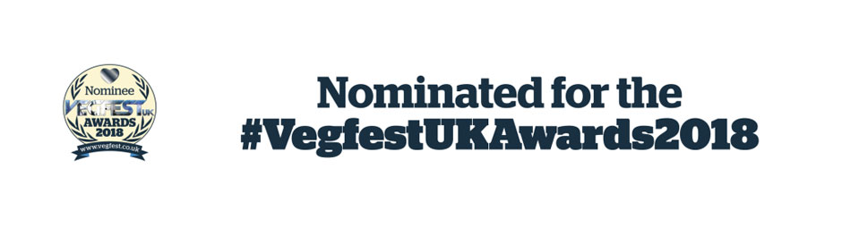 "Image contains a white background with a circular logo in the centre-left. Within the logo is a heart on the top and the words ""Nominee Vegfest UK Awards 2018"" below. On either side of the text, there are two sets of leaves. Below the circle, there is a small banner that says ""www.vegfest.co.uk"". To the right of the logo, there is black text that says ""Nominated for the"" on one line and ""#VegfestUKAwards2018"" on another."