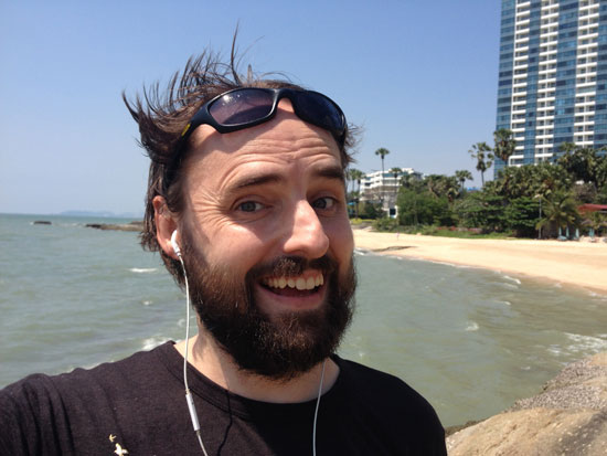 Image contains a smiling, bearded man with dark hair blowing in the wind. He's smiling and in the foreground while a sandy beach and palm trees can be seen in the background.