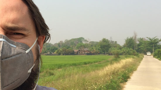 Image contains a photo of a man on the left-hand side wearing a face mask over his mouth and nose. To the right of the man, a hazy sky is visible above some trees in the horizon, a green rice field, and a narrow road.