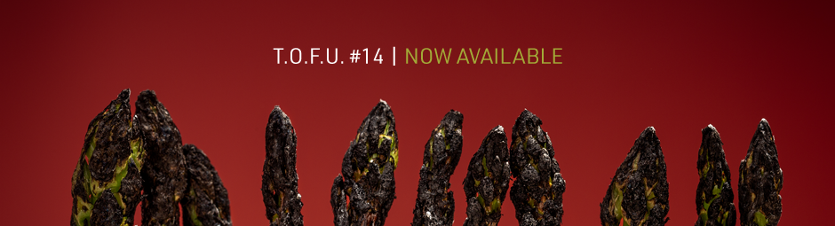 "Image contains a dark red background with a row of burnt asparagus tips along the bottom. Above the asparagus, there is white text that says ""T.O.F.U. #14 