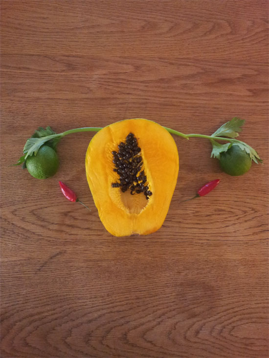Image contains a medium-dark brown wooden background. On the wood, there is a variety of fruit and vegetables. In the centre, there is a papaya and coming from the left and right of the fruit are two small stalks of a leafy green vegetable. Nestled under the leaves at the end of each stalk are lemons, and just below each lemon on the right and left there is a small hot pepper. The whole image is meant to represent the female reproductive system.